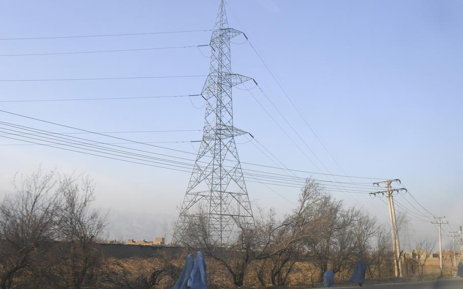 Afghan women are pictured here on Sunday, Dec. 24, 2017, donning the head-to-toe burqa as they walk along a highway in Parwan province, where power lines have been built under U.S.-funded contracts aimed at bringing economic development for rural areas and cheaper electricity to support outlying military posts.