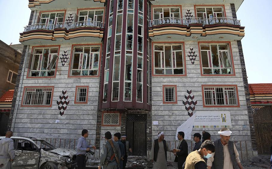 People gather outside a voter registration center which was attacked by a suicide bomber in Kabul, Afghanistan, Sunday, April 22, 2018.