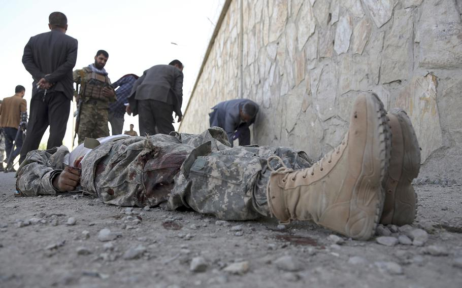 Security officials inspect the scene as a body of a militant fighter, wearing a U.S. military uniform, lies inside the Interior Ministry building after a deadly attack, in Kabul, Afghanistan, Wednesday, May 30, 2018.
