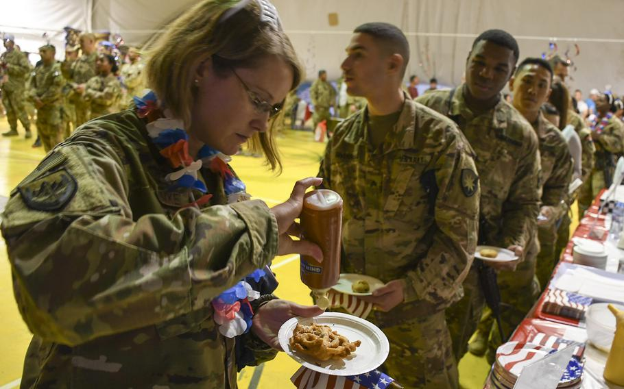 Air Force Maj. Amy Schimke, a cardiologist at Bagram's Craig Joint Theater Hospital, pours sauce on a funnel cake at a USO Independence Day event at Bagram Air Field on Friday, July 6, 2018.