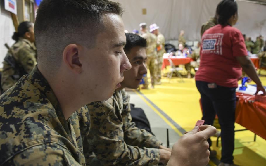 Marine Sgt. Robert Mastrocola, left, and Cpl. Arturo Velassquez wait to hear if their raffle numbers will be called, awarding them a chance to compete for a prize at a USO Independence Day event at Bagram Air Field on Friday, July 6, 2018.