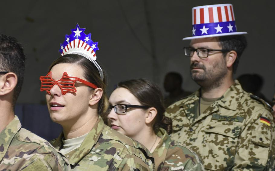Air Force Master Sgt. Marlena Lugo-Ruiz, of Jacksonville, Fla., shows her holiday spirit with star sunglasses and a red, white and blue tiara as she waits for fried Oreos and funnel cake at a USO Independence Day event at Bagram Air Field on Friday, July 6, 2018.