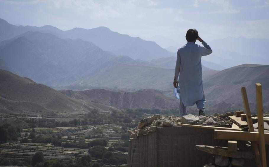Eman, 20, a member of the Afghan Local Police, watches over a key valley from his checkpoint in Deh Bala district in Nangarhar province, Afghanistan, on Saturday,  July 7, 2018.
