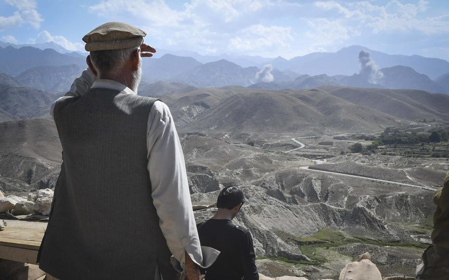 A member of the Afghan Local Police watches the aftermath of bombings by American F-16 fighter-bombers against a key valley in Deh Bala district in Nangarhar province, Afghanistan, Saturday,  July 7, 2018.