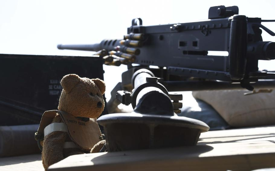 """A """"safety bear"""" wears its protective cardboard vest as it guards an M-240B machine gun at the American special forces side of a checkpoint jointly held with Afghan commandos in Deh Bala district in The 3rd Battalion, 1st Special Forces Group assisted Afghan security forces in operations beginning in April and ending in June to capture Gurgoray, the purported capital of Islamic State fighters in the region, military officials said."""