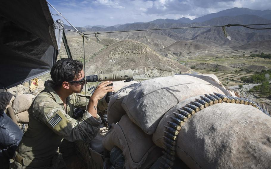 A Special Forces soldier peers through a scope while manning Observation Post Krakken, a checkpoint overlooking a key valley in Deh Bala district in Nangarhar province on Saturday, July 7, 2018.