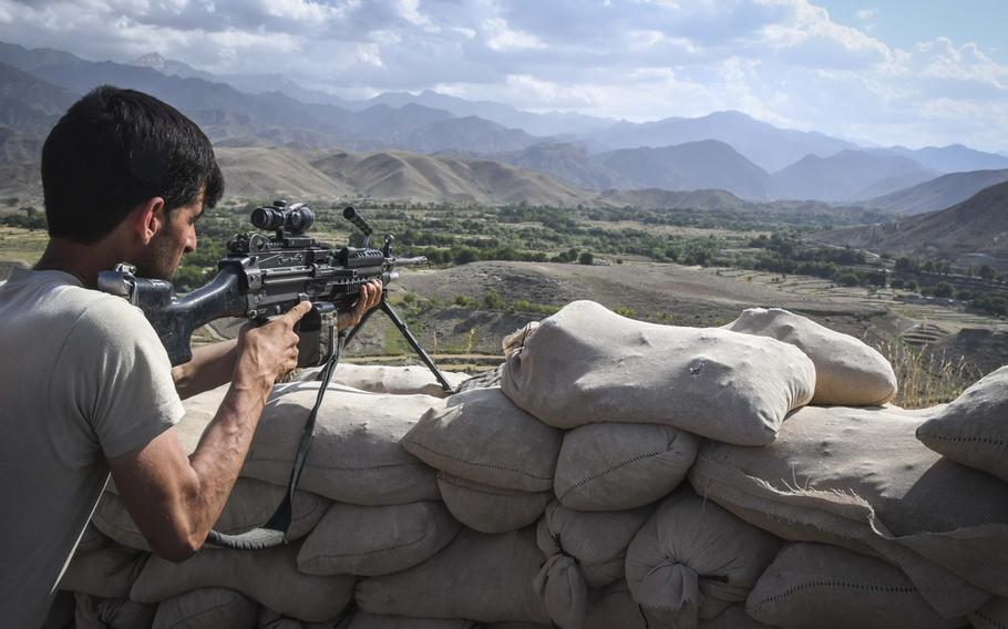 Khairullah, 30, an Afghan commando, sights an M-249 light machine gun at Observation Post Krakken, a checkpoint overlooking a key valley in Deh Bala district in Nangarhar province on Saturday, July 7, 2018.