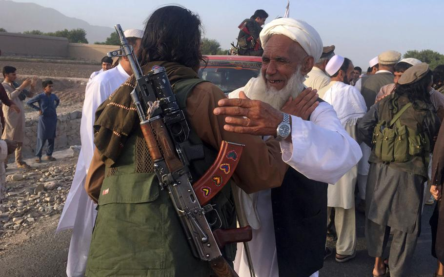 In this June 16, 2018 file photo, Taliban fighters gather with residents to celebrate a three-day cease fire marking the Islamic holiday of Eid al-Fitr, in Nangarhar province, east of Kabul, Afghanistan. On Sunday, Aug. 19, 2018, Afghan President Ashraf Ghani announced a conditional cease-fire with Taliban insurgents for the duration of the Eid al-Adha holiday. Ghani made the announcement Sunday during celebrations of the 99th anniversary of Afghanistan's independence.