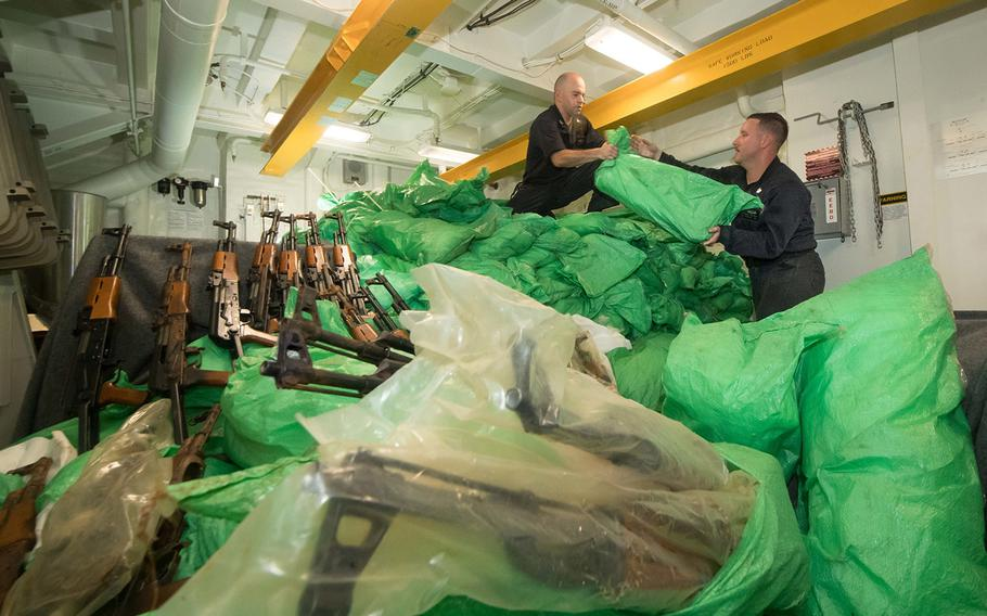 Petty Officer 1st Class Griffin Vancil, left, and Petty Officer 1st Class Devan Wallswolf stack a cache of over 1,000 AK-47 automatic rifles aboard the guided-missile destroyer USS Jason Dunham on Aug. 30, 2018. The ship's visit, board, search and seizure team seized the weapons from a skiff during a flag verification boarding near Yemen as part of maritime security operations.