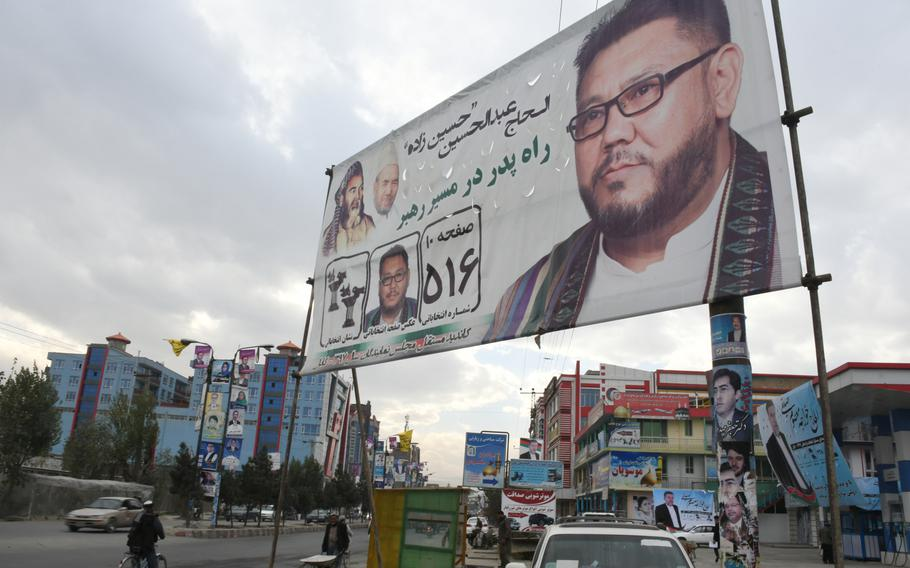 An election poster for a Hazara parliamentary candidate stands next to a main road in the Dasht-e-Barchi neighborhood of Kabul, Afghanistan, on Tuesday, Oct. 16, 2018.
