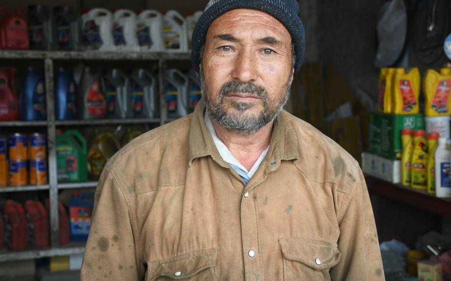 Rajab Ali, a mechanic who lives and works in Kabul's Dasht-e-Barchi neighborhood, stands in his garage on Tuesday, Oct. 16, 2018. Ali says he's upset Afghan and U.S. forces have been unable to prevent the Islamic State group from operating in the country.