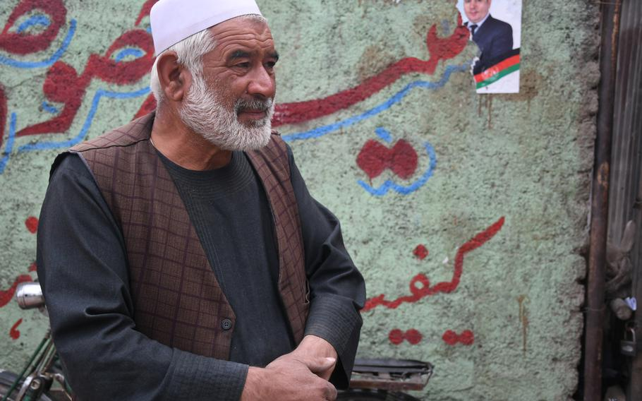 Dil Mohammad stands outside his shop in the Dasht-e-Barchi neighborhood of Kabul on Tuesday, Oct. 16, 2018, and explains how he will participate in upcoming parliamentary elections in the hope that it will make the area safer.
