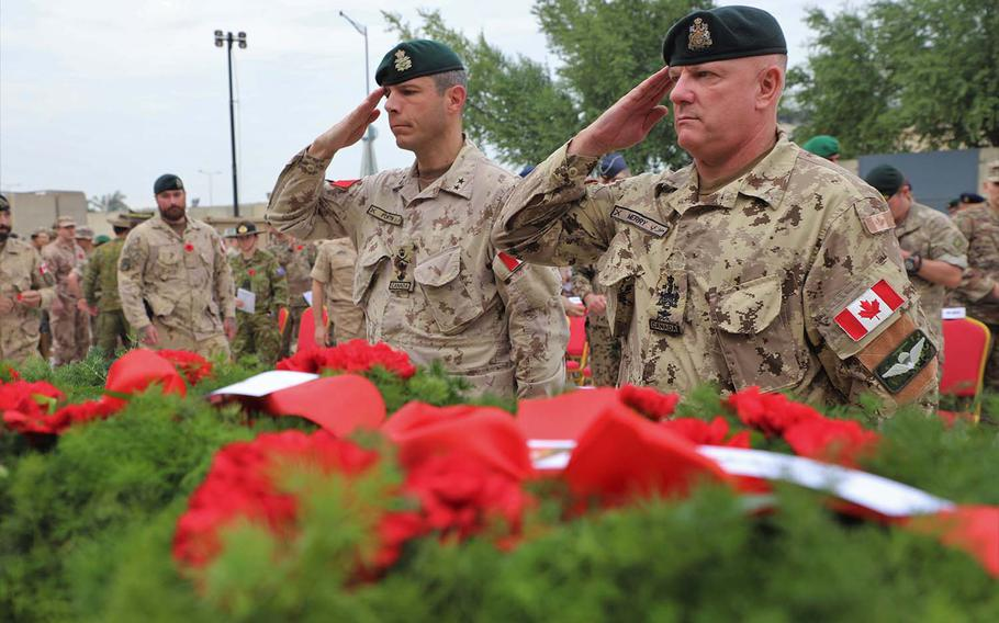 Canadian Armed Forces Major-General Dany Fortin, left, commander of the 1st Canadian Division Headquarters, and Sen. Appointment Chief Warrant Officer Merry salute and show their respect to a centerpiece covered in memorial reefs at the Armistice Ceremony at Union III, Baghdad on Nov. 11, 2018.