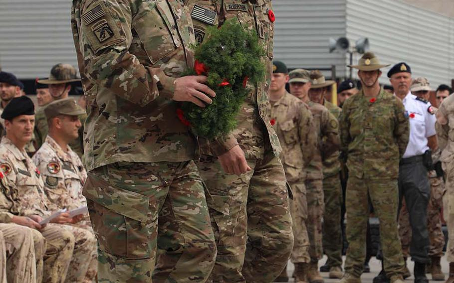 U.S. Army Lt. Gen. Paul LaCamera, left, commander of the 18th Airborne Corps and Combined Joint Task Force - Operation Inherent Resolve (CJTF-OIR), and Command Sgt. Maj. Charles Albertson walk towards the center of the ceremony with a wreath to be placed on a centerpiece at the Armistice Ceremony at Union III, Baghdad on Nov. 11, 2018.
