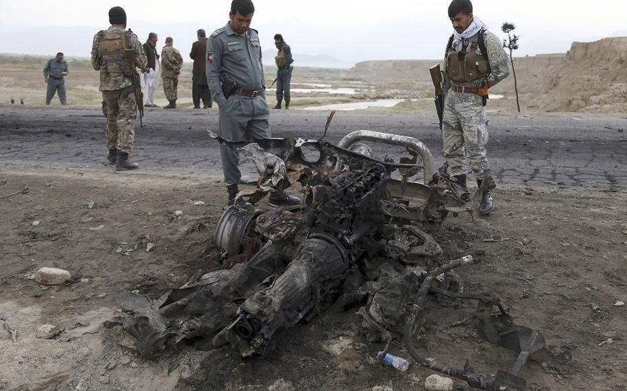 Afghan security forces gather at the site of Monday's suicide attack near the Bagram Air Field, north of Kabul, Afghanistan, Tuesday, April 9, 2019. Three American servicemembers and a U.S. contractor were killed when their convoy hit a roadside bomb on Monday near the base.