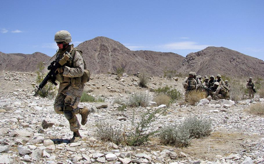 Then Lance Cpl. Christopher Slutman, left, rushes across a danger area with his platoon through a fire and maneuver course on Range 400, at Twentynine Palms, Calif., on June 30, 2008.