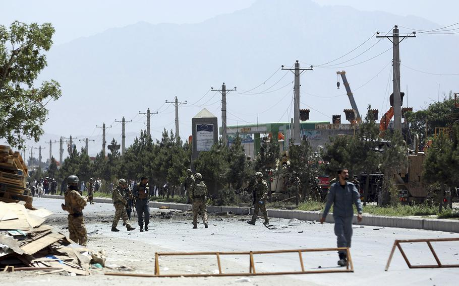 NATO and Afghan forces gather at the site of a suicide car bomb in Kabul, Afghanistan, Friday, May 31, 2019. In a second suicide attack in as many days to rattle the Afghan capital, a car bomb targeting a U.S. convoy exploded early Friday morning in an eastern neighborhood, police said.