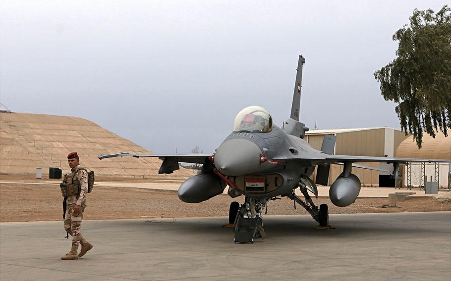 An Iraqi soldier stands guard near a U.S.-made Iraqi Air Force F-16 fighter jet at Balad Air Base, Iraq, on Tuesday, Feb. 13, 2018.