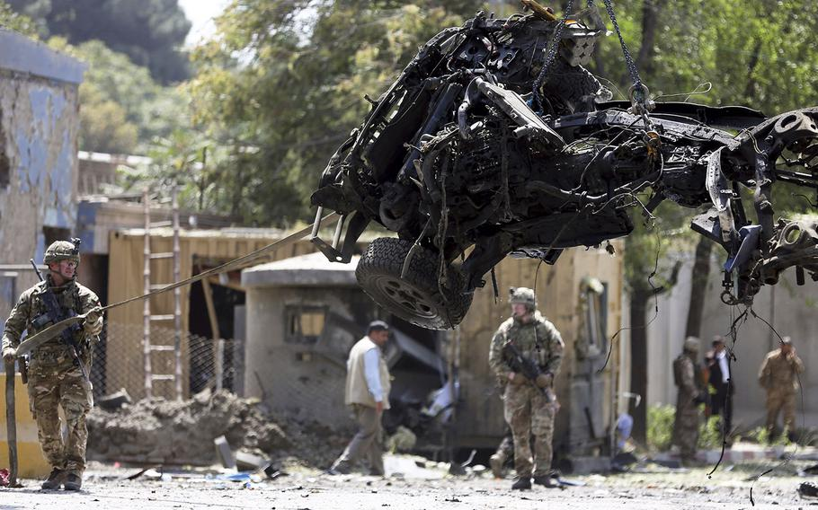 Resolute Support forces remove a damaged vehicle after a car bomb explosion in Kabul, Afghanistan, Thursday, Sept. 5, 2019.