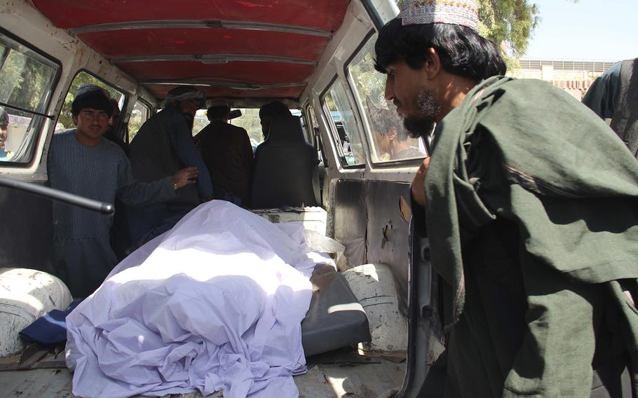 Afghans transport the body of a woman who was killed during a raid conducted by Afghan special forces, in the southern Helmand province, Monday, Sept. 23, 2019.