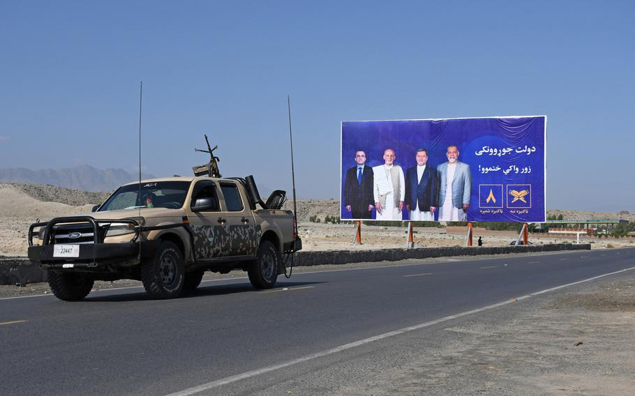 An Afghan military vehicle drives past a campaign sign for President Ashraf Ghani in Laghman province, Afghanistan, on Aug. 18, 2019.