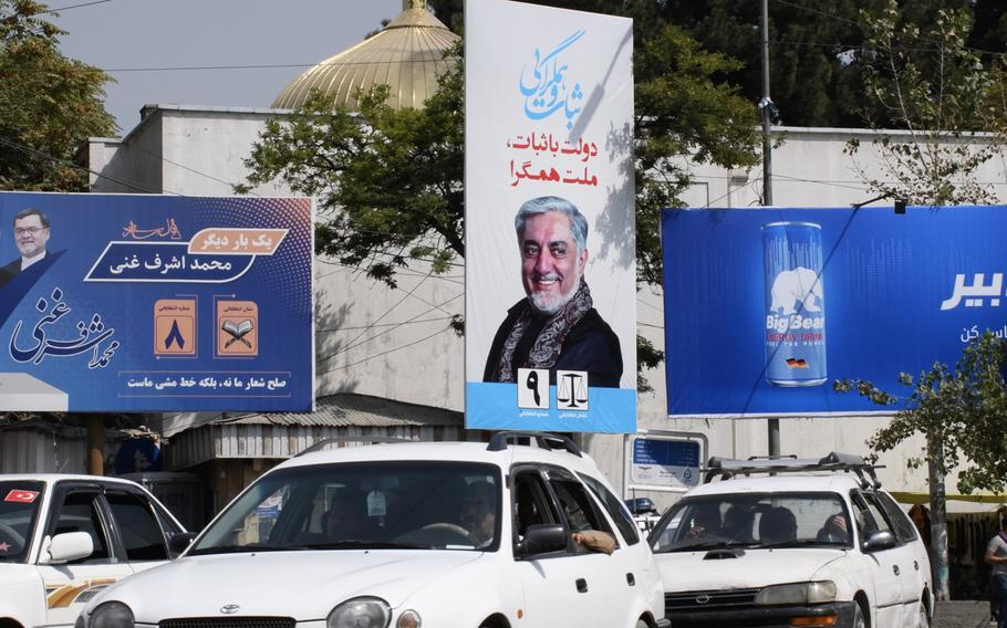 Cars in Kabul drive past campaign billboards in Kabul for the two frontrunners in Afghanistan's presidential election, which is to be held on Saturday, Sept. 28, 2019.