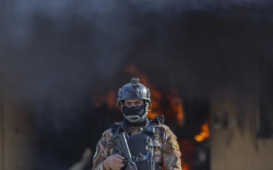 An Iraqi soldier stands guard in front of smoke rising from a fire set by pro-Iranian militiamen and their supporters in the U.S. embassy compound, Baghdad, Iraq, Wednesday, Jan. 1, 2020.