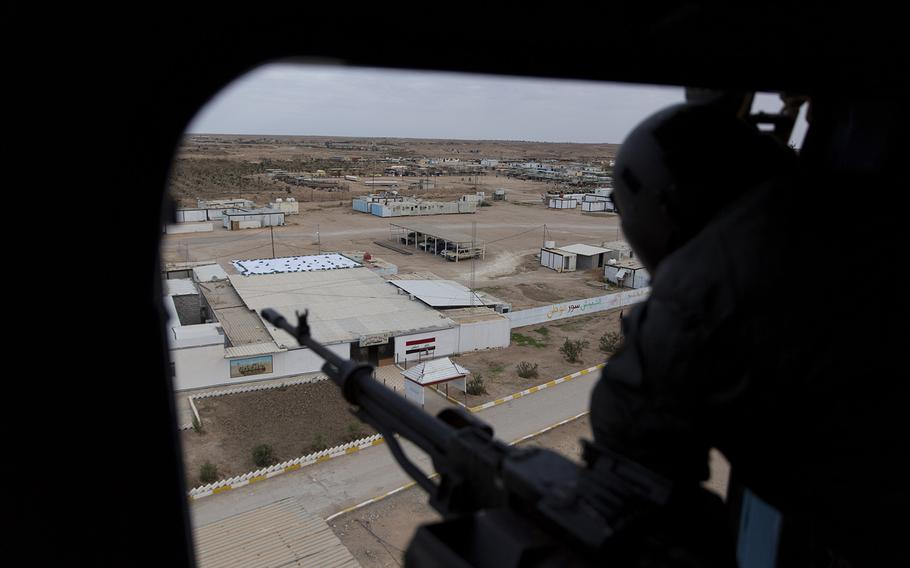 An Iraqi soldier mans a machine gun aboard a helicopter during military operations in Anbar, Iraq, on Dec. 29, 2019. An Iraqi general said security had been beefed up around the Ain al-Asad air base, a sprawling complex in the western Anbar desert that hosts U.S. forces, following a series of attacks. On Saturday, Jan. 4, 2020, the U.S.-led coalition in Iraq suspended training with government security forces following the targeted killing of Iranian Maj. Gen. Qassem Soleimani in Baghdad on Friday.