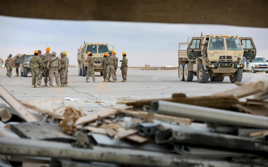 Soldiers, airmen and civilian contractors remove debris from recent missile attacks at al Asad Air Base, Iraq, Jan. 12, 2020.