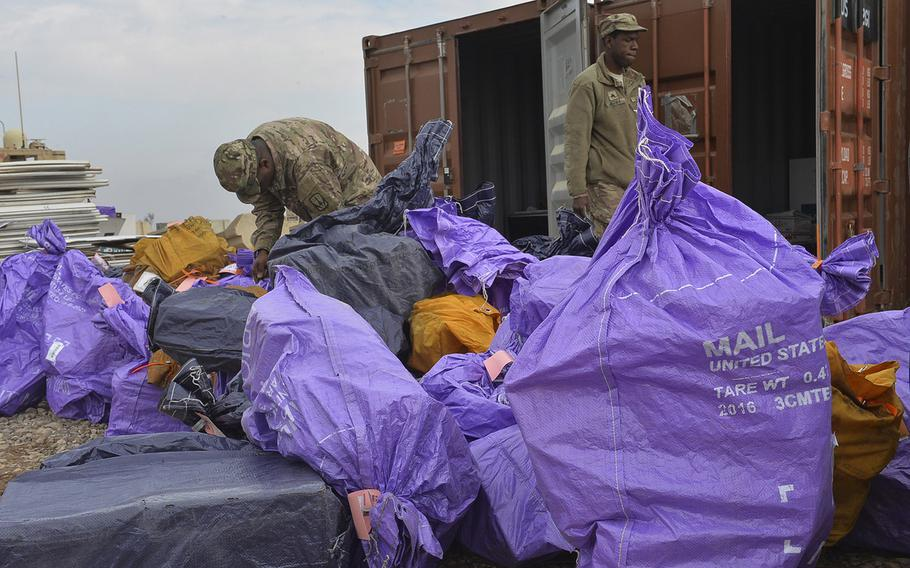 Sgt. Alvin Bethea Jr. walks past a pile of mailbags being sorted on Qayara Airfield West, March 17, 2017.
