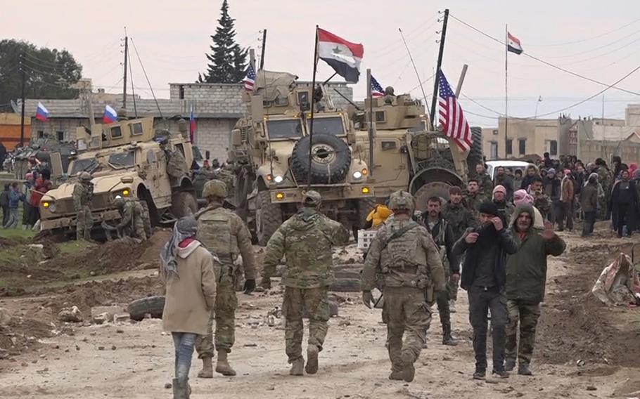 In this frame grab from video, Russian, Syrian and others gather next to an American military convoy stuck in the village of Khirbet Ammu, east of Qamishli city, Syria, Wednesday, Feb. 12, 2020. Syrian media and activists say a Syrian was killed and another wounded in a rare clash between American troops and a group of government supporters in northeast Syria.