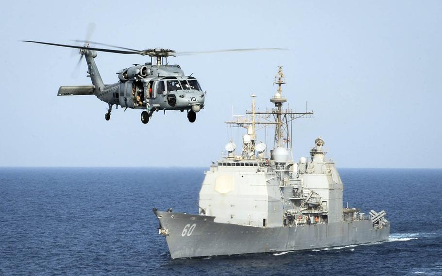 An HH-60H Sea Hawk helicopter passes the guided-missile cruiser USS Normandy in the Arabian Gulf in September 2015.