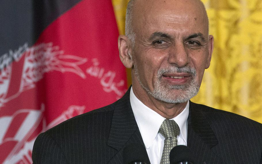 President Ashraf Ghani of Afghanistan stands in front of his nation's flag during a news conference at the White House in 2015.