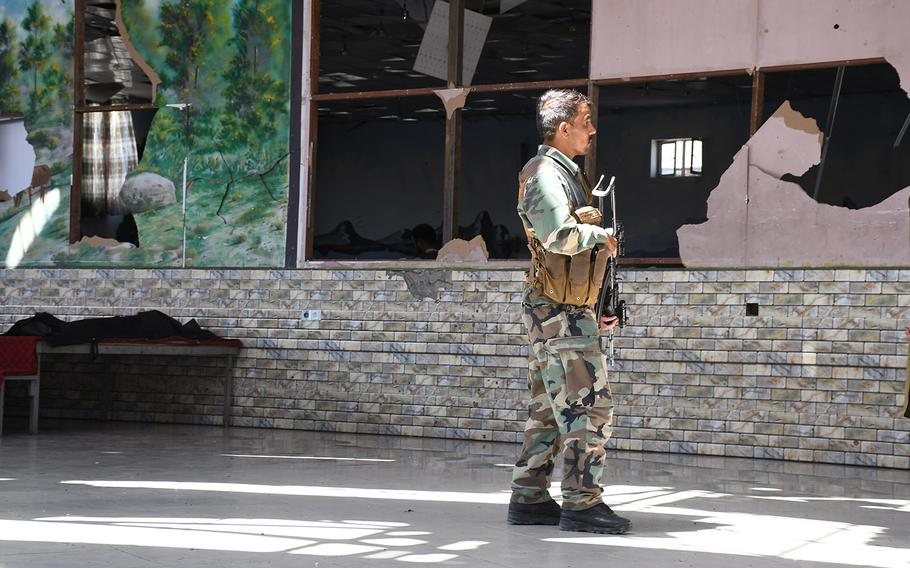 An Afghan security official patrols the Dubai City Wedding Hall in Kabul on Aug. 18, 2019, a day after a suicide attack at the venue killed dozens of people.