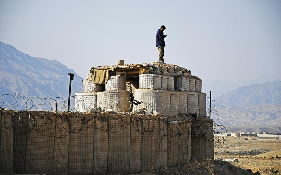 An Afghan soldier checks his cellphone on Saturday, Feb. 22, 2020, atop the walls of his base, just east of Kabul, during the first day of an agreed reduction of violence between the Taliban and the U.S. forces. Government forces are also to stand down, said Gawhar Khan Baburi, the district governor of Surobi.