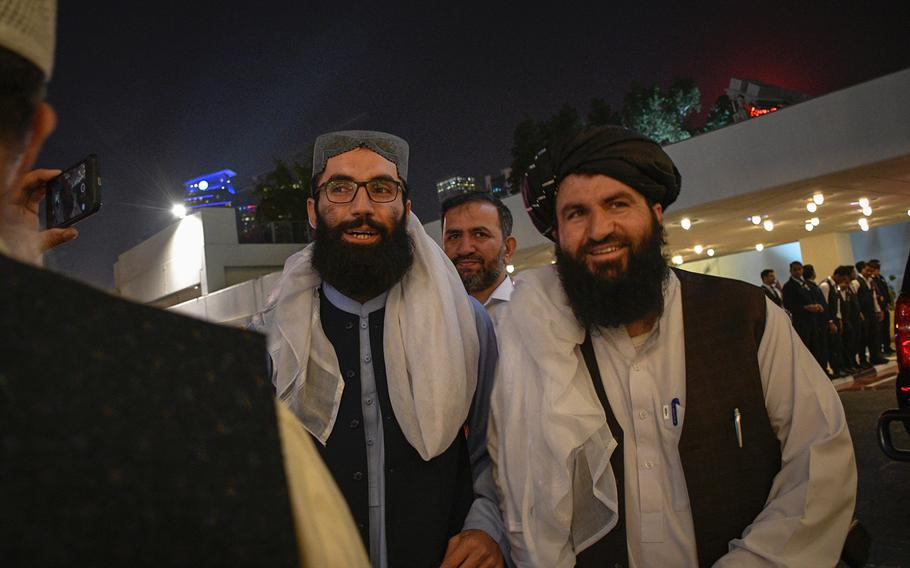 High-ranking Taliban official Anas Haqqani, left, and a press aide for the group meet with reporters on the eve of a historic agreement between the militant group and the United States in Doha, Qatar, Feb. 28, 2020.