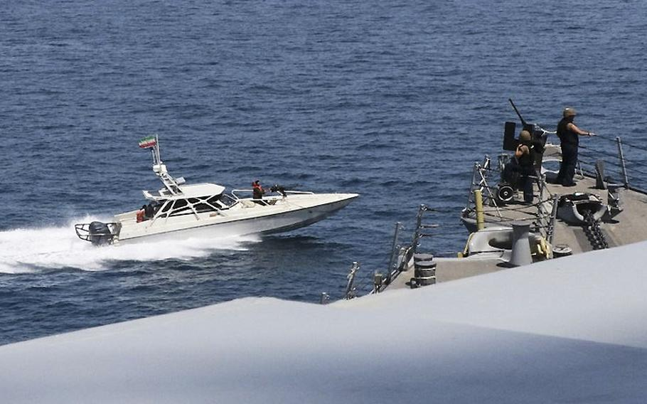 A U.S. Navy photo shows a boat flying the Iranian flag next to a U.S. ship in the Persian Gulf, April 15, 2020.