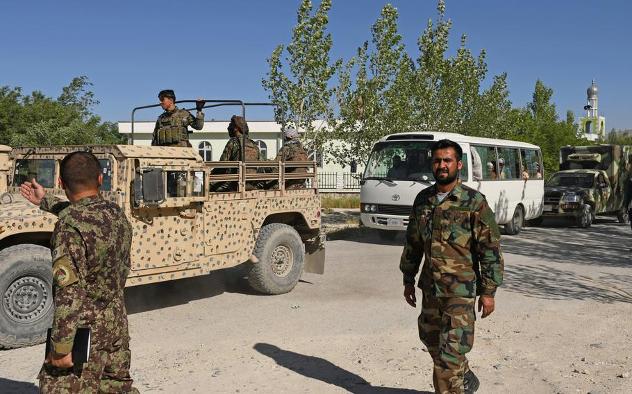Afghan security forces escort buses of recently freed Taliban soldiers away from Bagram prison on May 26, 2020. The Taliban have demanded 5,000 of their fighters be released before starting peace talks with the government. The country's president said Thursday that they will do so.