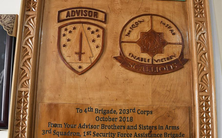 A plaque given to Brig. Gen. Abdul Raziq, then-commander of the Afghan army's 4th Brigade, 203rd Corps, by the 1st Security Force Assistance Brigade, hung in Camp Maiwand in Logar province south of Kabul, Afghanistan. U.S. Army Command Sgt. Maj. Timothy Bolyard was killed in an insider attack after a meeting with the general on Sept. 3, 2018.