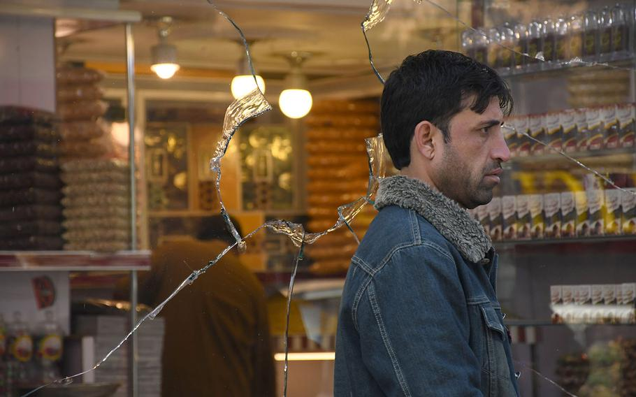 A man walks past a shop window in Kabul shattered by rocket blasts on Saturday, Nov. 21, 2020.