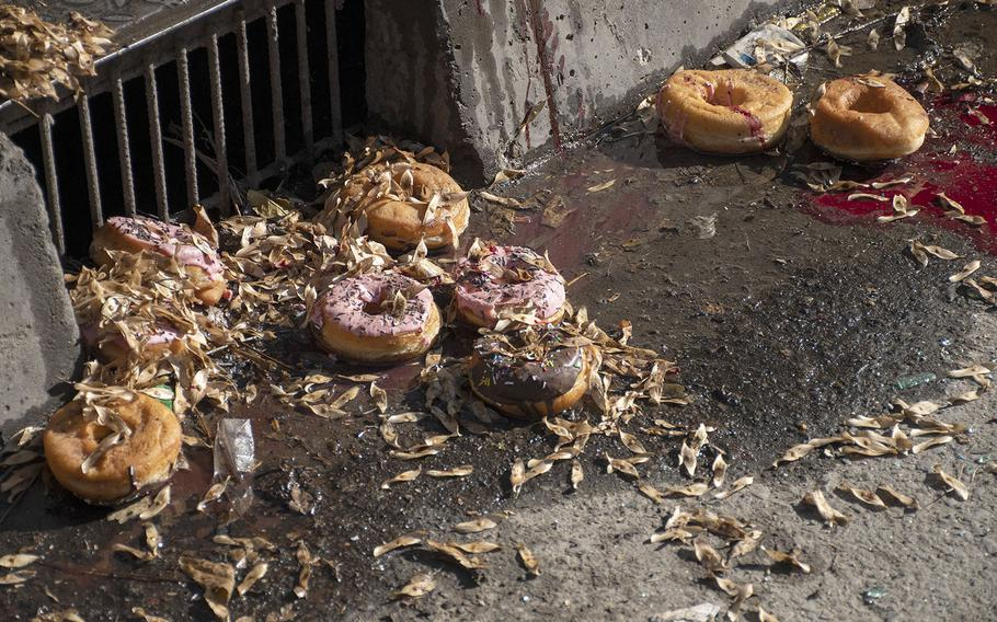 Donuts litter the street in Kabul's Shar-e-Now neighborhood on Saturday, Nov. 21, 2020, after a rocket attack damaged several shops in the area and destroyed a bakery van.