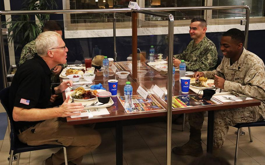 Acting Defense Secretary Christopher Miller, left, speaks with Marine Sgt. Joshua Jackson, right, with Fleet Logistics Center at Naval Support Activity Bahrain over a Thanksgiving meal Nov. 25, 2020. Miller is visiting troops in the Middle East for the Thanksgiving holiday.