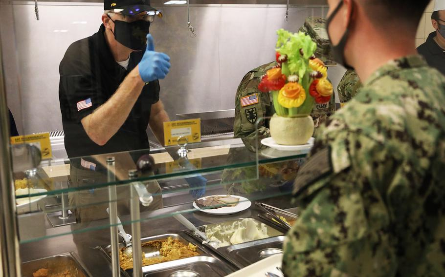 Acting Defense Secretary Christopher Miller gives a thumbs up to a sailor while serving a Thanksgiving meal at Naval Support Activity Bahrain Nov. 25, 2020. Miller is visiting troops in the Middle East for the Thanksgiving holiday.
