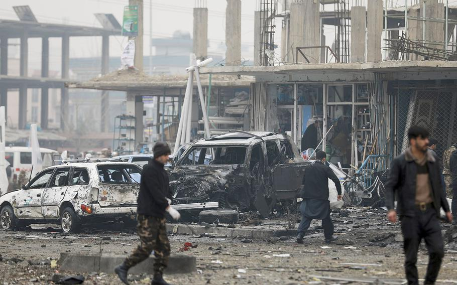 Afghan security personnel inspect the site of a bombing attack in Kabul, Afghanistan, Sunday, Dec. 20, 2020.