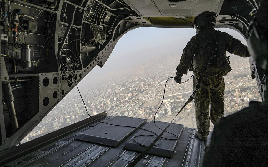 A U.S. soldier looks out the back of a CH-47 Chinook helicopter as it flies over Kabul on the way to Resolute Support Headquarters on Dec. 22, 2020.