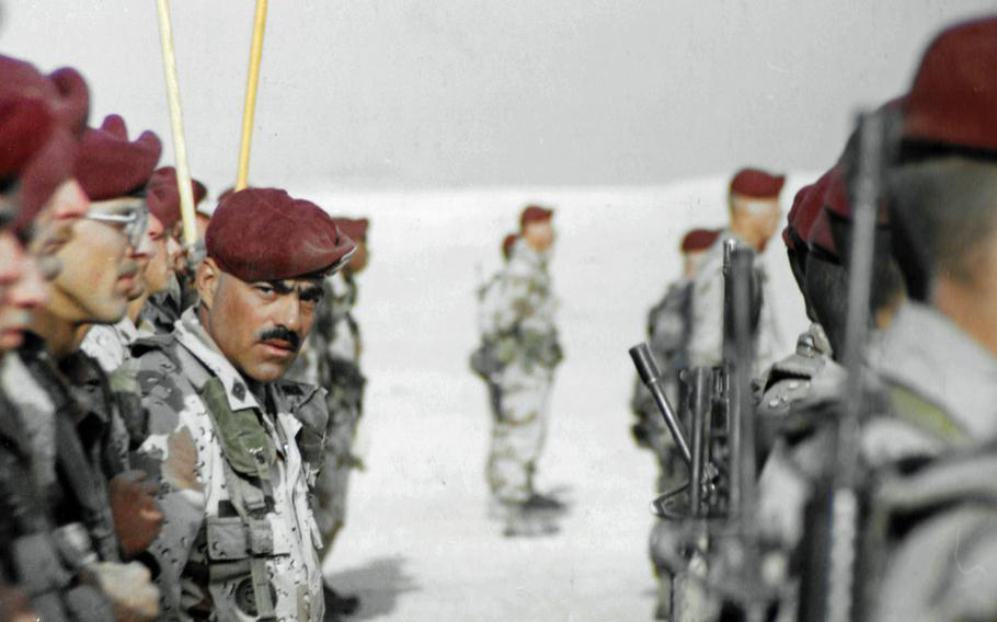 Looking at the photographer, 1st Sgt. Fred Ferryerra stands in formation during a ceremony on Christmas Day 1990.
