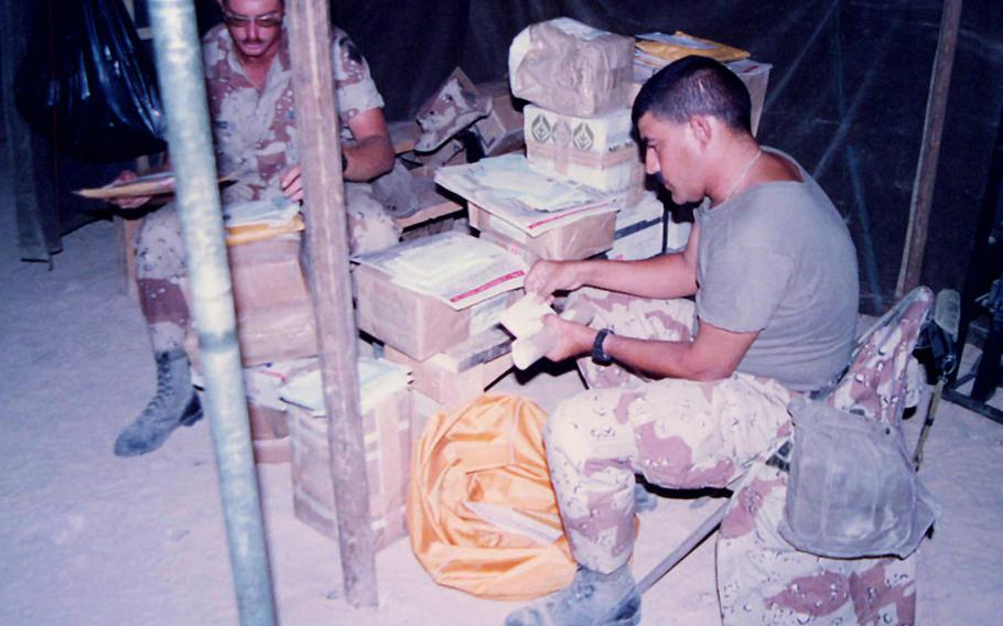 Soldiers open care packages while deployed to the Middle East as part of Operations Desert Shield and Desert Storm.
