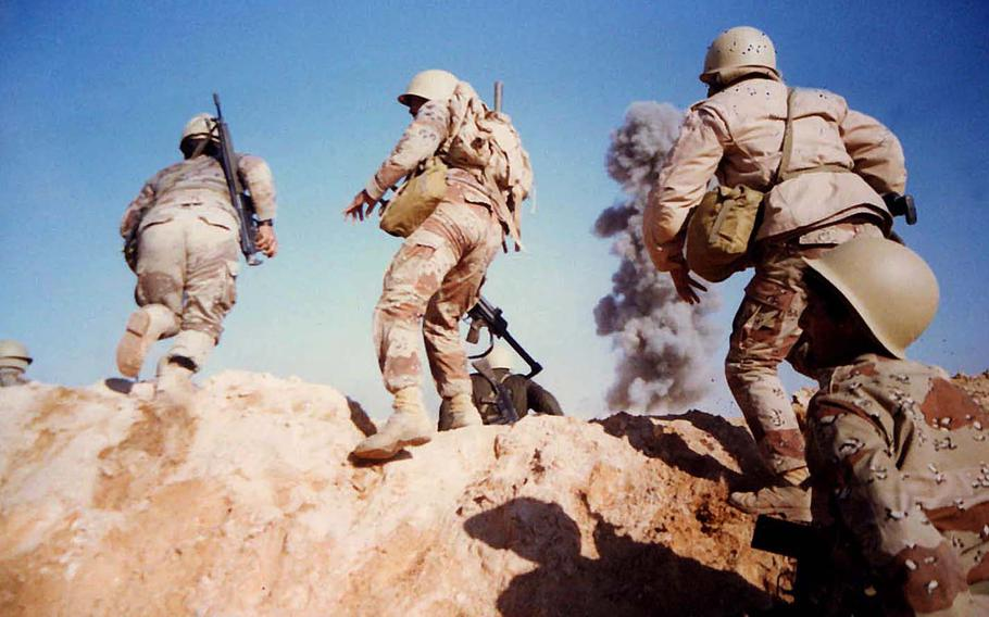 Smoke billows in the distance as soldiers rush forward in a photo taken by Army Sgt. Kirby Lee Vaughn while deployed during the Gulf War, which lasted from Aug. 2, 1990, to Feb. 28, 1991.