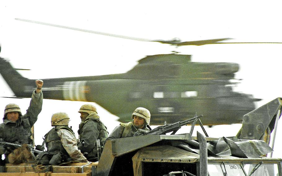 An allied helicopter flies past U.S. troops moving to the Iraqi border to begin the Operation Desert Storm ground assault in February 1991.
