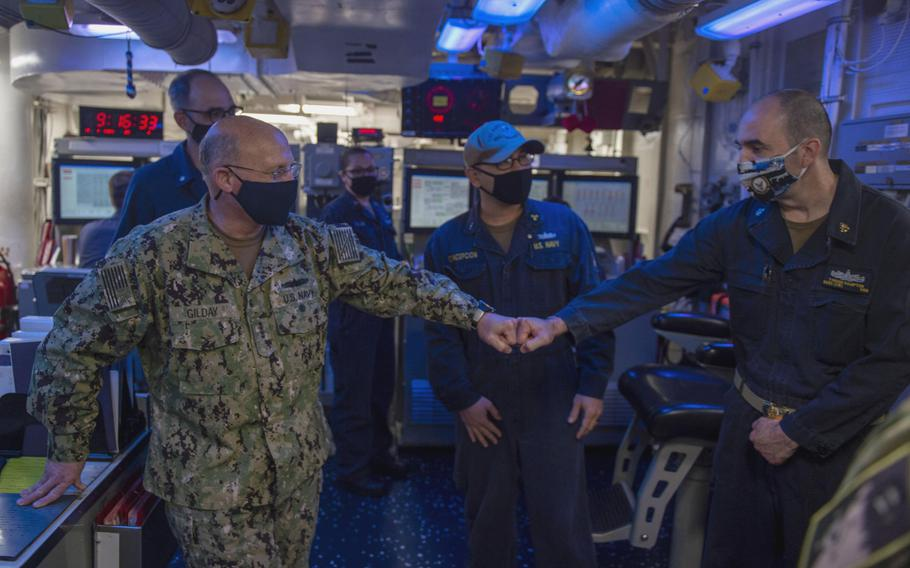 Adm. Mike Gilday, chief of naval operations, left, greets Chief Petty Officer Tyronn Hampton aboard the destroyer USS John Paul Jones in the Persian Gulf, Jan. 13, 2021.
